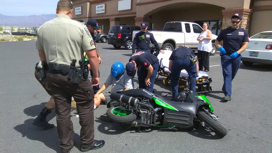 Selwyn Harris/Pahrump Valley Times  Pahrump Valley Fire and Rescue crews medically assess a man who crashed while on a scooter in the parking lot of the DMV office on East Basin Avenue on Tuesday  ...