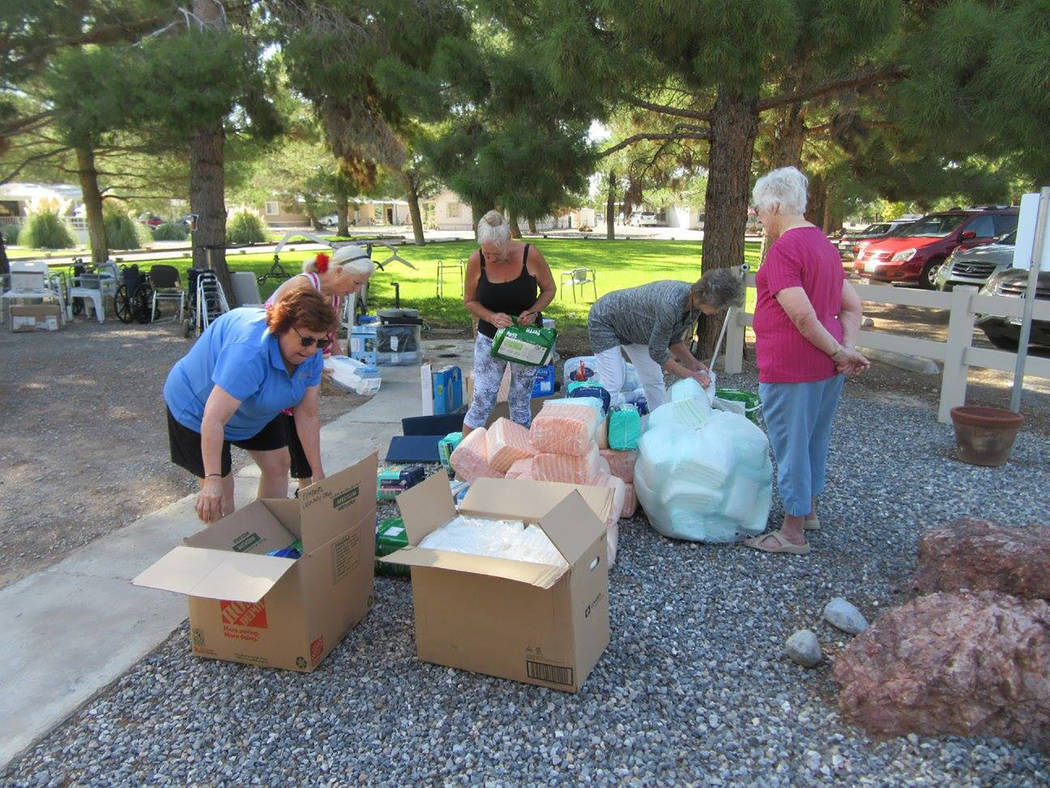 Selwyn Harris/Pahrump Valley Times  A handful of senior center visitors assist LaaRee Drawantz by helping to unload the supplies. The center had a steady stream of seniors who were grateful for th ...
