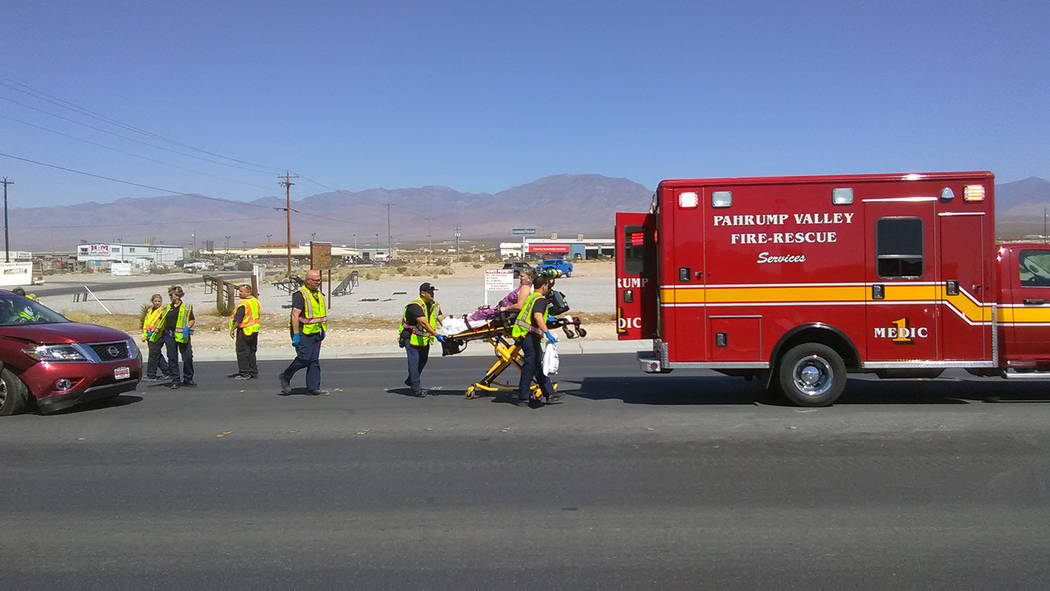 Selwyn Harris/Pahrump Valley Times  Pahrump EMS crews prepare to transport a woman to Desert View Hospital following a two-vehicle collision along Highway 160 at Wilson Road.