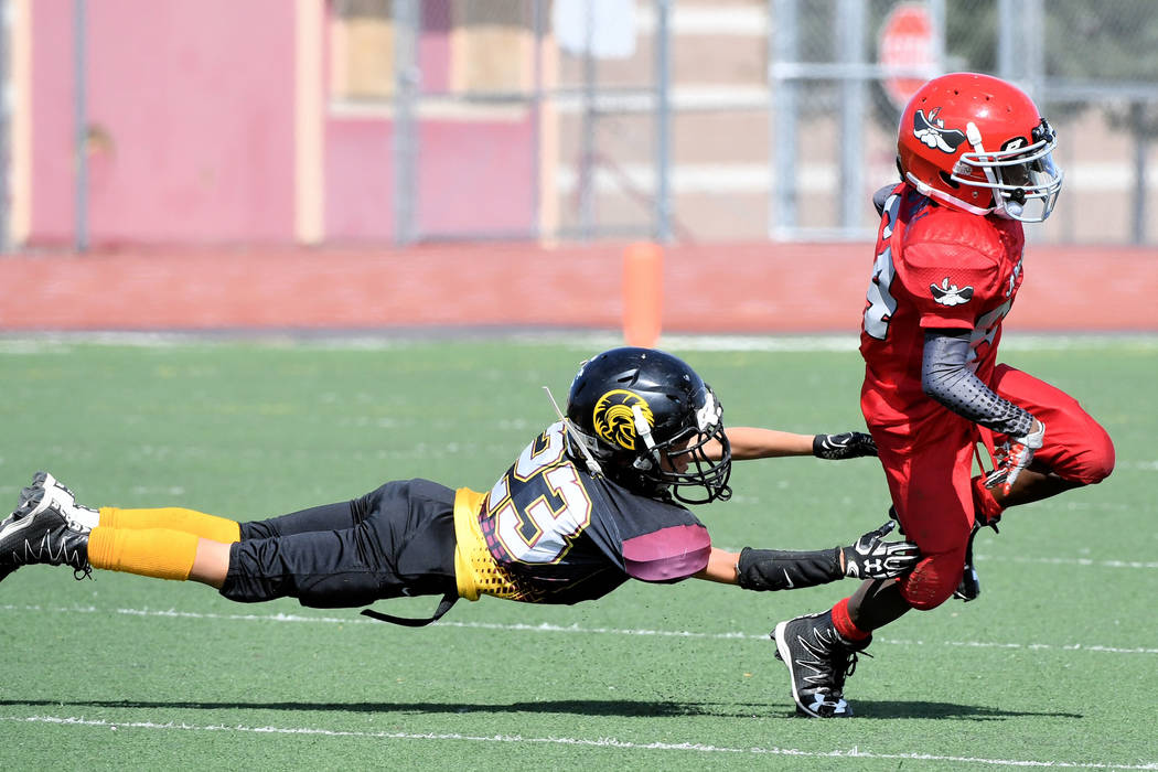 Peter Davis/Special to the Pahrump Valley Times  This is a funny way to catch a ride. But in all seriousness, Cade Wulfenstein made this tackle for his 9U team.