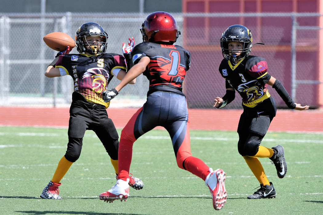 Peter Davis/Special to the Pahrump Valley Times  Gunner Cortez, 11U Trojans, with the ball as he looks for a receiver downfield.