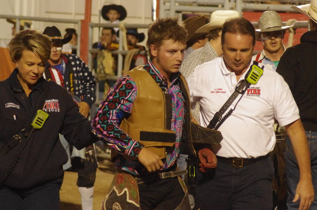 Vern Hee/Pahrump Valley Times Boom, boom out goes the lights. Chief Scott Lewis helps a bullrider off after a bad fall.