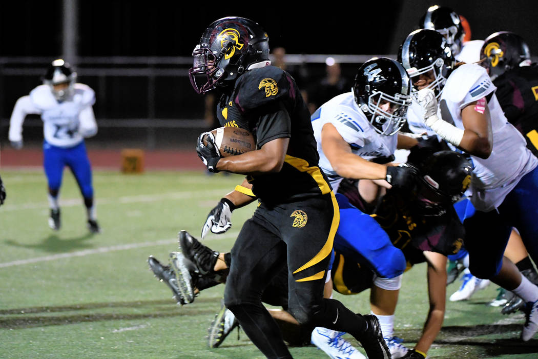 At left, Junior Trojans running back DeAngelo Brown runs the ball downfield against the visiting Jaguars last Friday. Brown had several long runs and the Trojans were able to run up the middle aga ...