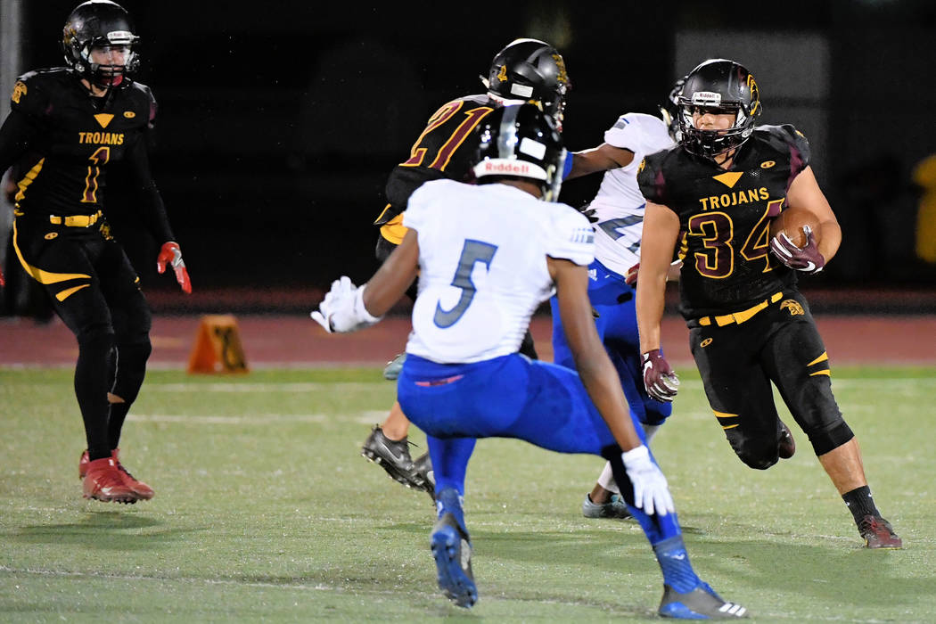 Junior Trojans running back Nico Velazquez runs with the ball against Desert Pines last Friday. The Trojans were able to run against the defending state champions.