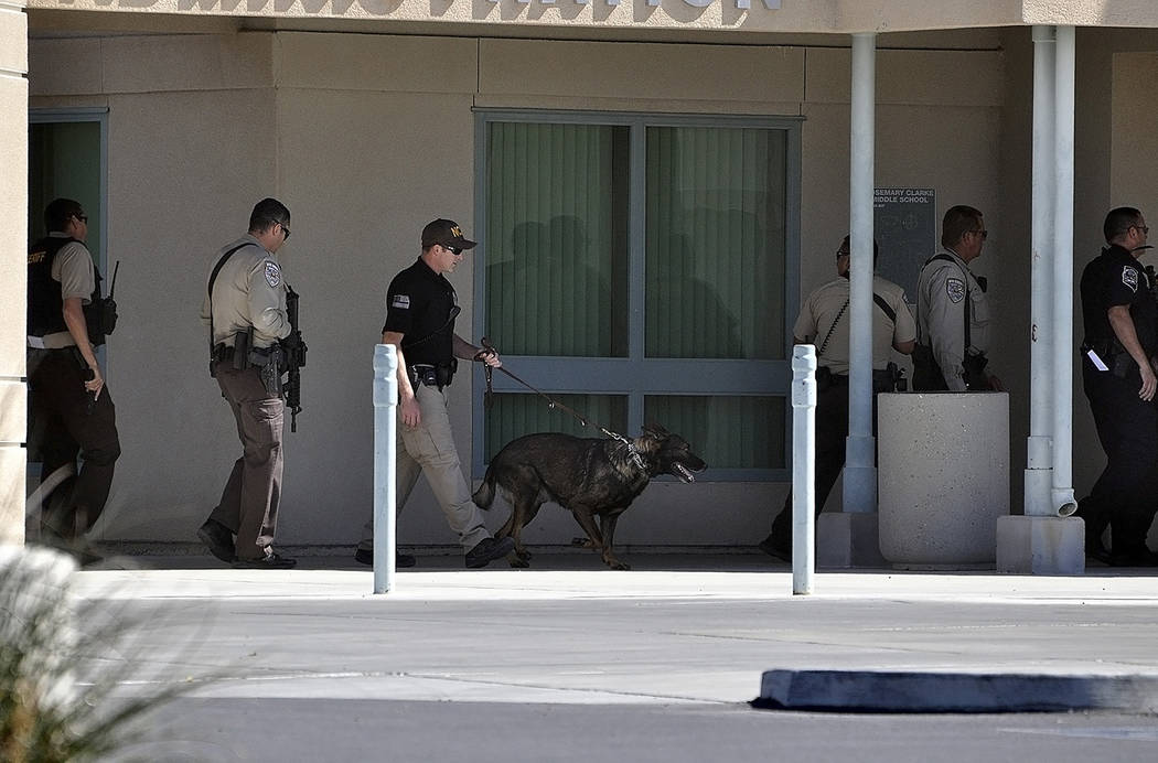 Horace Langford Jr./Pahrump Valley Times  Nye County Sheriff's deputies armed with rifles and a K-9, prepare to search Rosemary Clarke Middle School in search of wanted suspect Duane Johnson, wh ...