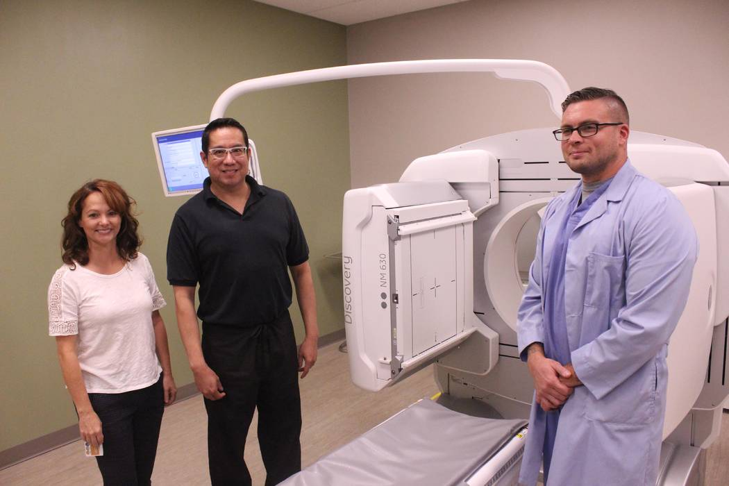 Jeffrey Meehan/Pahrump Valley Times Vicki Thornhill, CT supervisor at Desert Radiologists (left), and John Garcia (center) and Todd Winchell (right), stand in front a General Electric NM630 machin ...