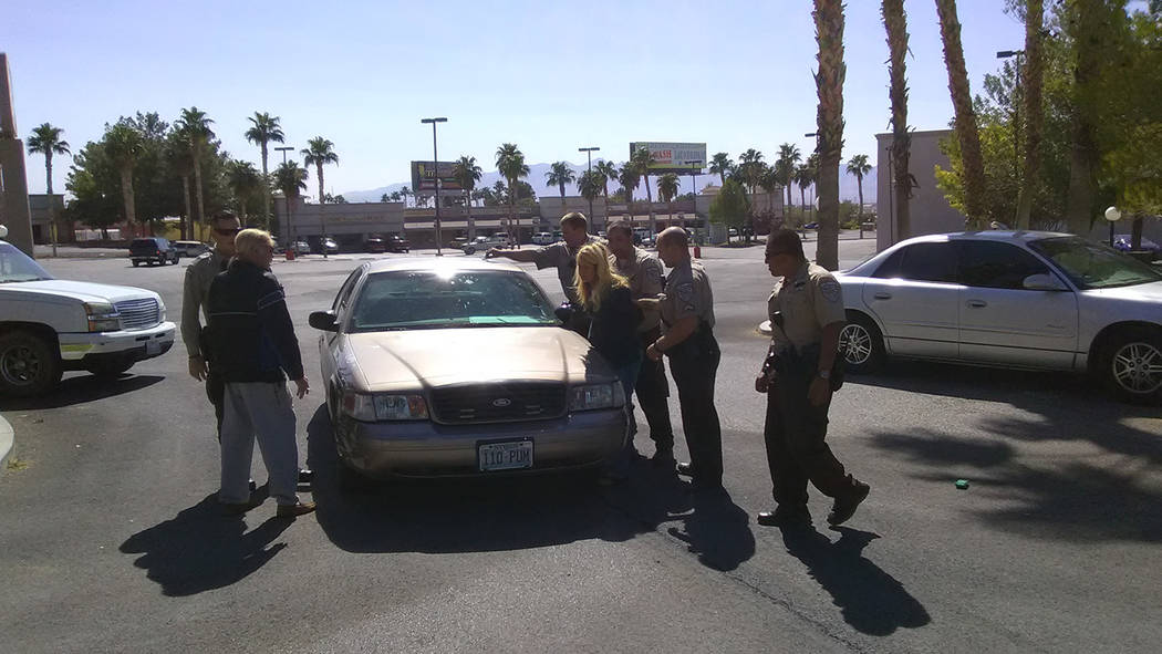 Selwyn Harris/Pahrump Valley Times Nye County Sheriff's deputies place a woman under arrest after allegedly brandishing a firearm at landscaping crews early Wednesday afternoon at the Best Western ...