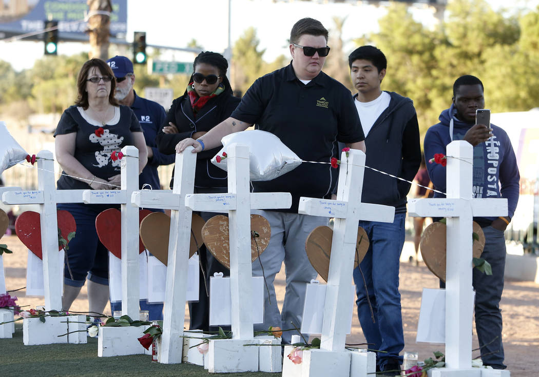 Bizuayehu Tesfaye/Las Vegas Review-Journal People gather on Oct. 6, 2017, in Las Vegas where 58 white crosses stand to honor the victims of the Oct. 1 mass shooting.