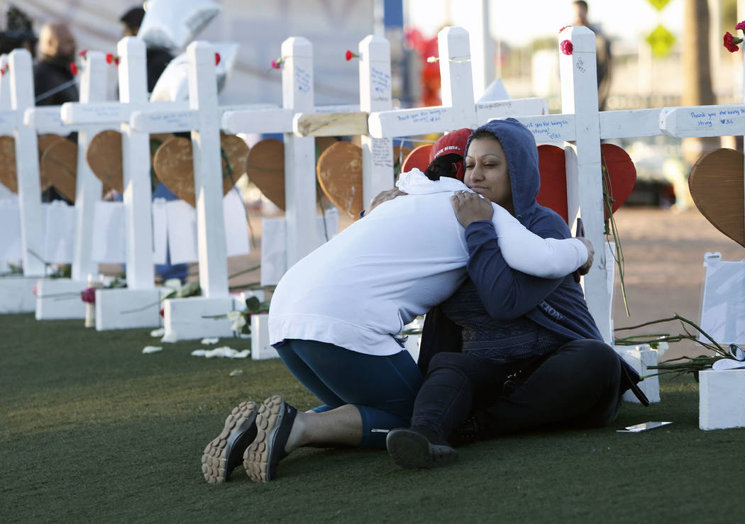 Bizuayehu Tesfaye/ Las Vegas Review-Journal  Shelley Boyle, left, and Cece Navarrette comfort each other on the Las Vegas Strip where fifty-eight white crosses stand to honor the victims of Sunday ...
