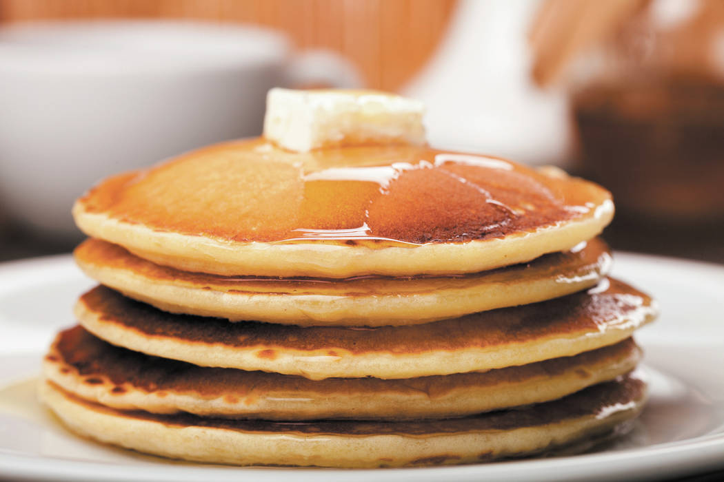 Panckes with butter and syrup with coffee in the background