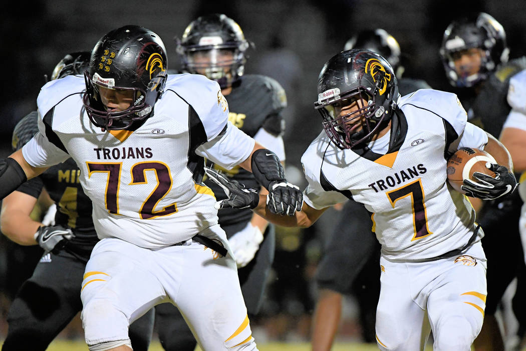 Peter Davis/Special to the Pahrump Valley Times  DeAngelo Brown looks for a hole in the Sunrise Mountain line with Caleb Sproul in the lead. Brown was held to just 60 yards. The Trojans had 192 ya ...