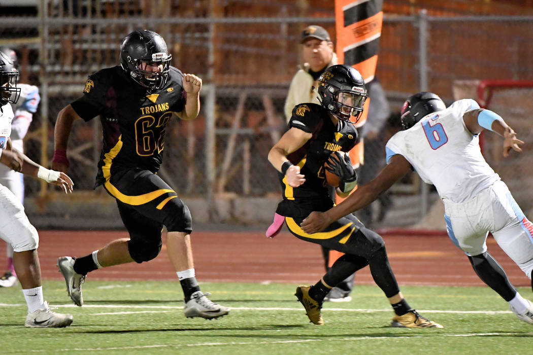 Peter Davis/ Special to the Pahrump Valley Times Senior quarterback Dylan Coffman runs for extra yardage on Friday night. Coffman had a 49-yard TD run in the first quarter to get the Trojans on th ...