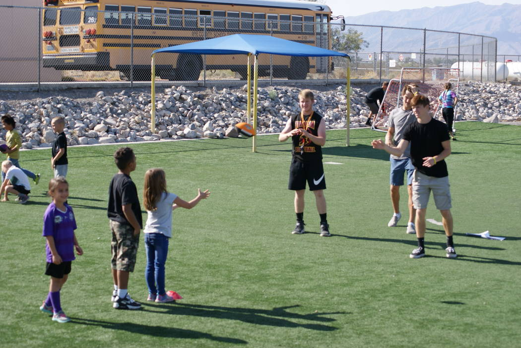 Alexis Norman/PVHS journalism class From left to right: Senior football players David Roundy, Cory Bergan and Dylan Coffman toss a football with a group of Hafen Elementary students on Oct. 19. Ov ...