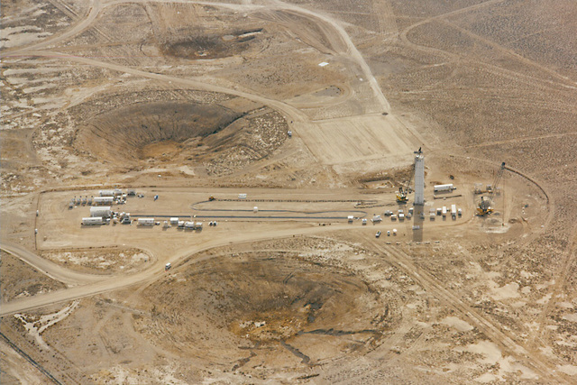 Final test preparations at a drill site on the DOE's Nevada Test Site. Prior craters from underground tests dot the landscape. October 1981. (National Nuclear Security Administration)