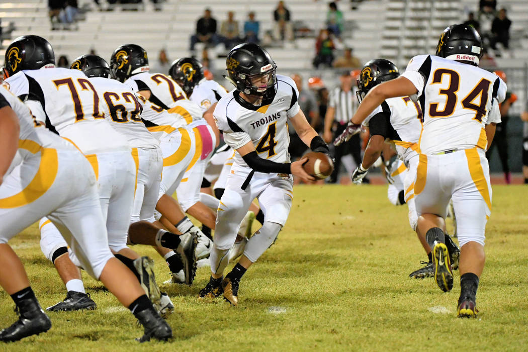 Peter Davis/ Special to the Pahrump Valley Times Dylan Coffman hands the ball off to DeAngelo Brown during the Mojave game on Friday. Note the line holding, and no penetration from Mojave's line.