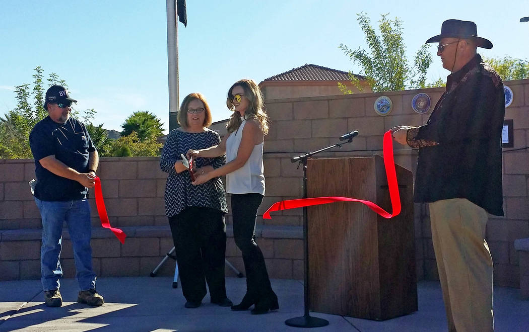 Elaine Richardson cuts the ribbon at the dedication of the Robert A. and Florence Revert Park in Beatty. The ends of the ribbon are being held by Beatty Town Advisory Board members Kelly Carroll ( ...