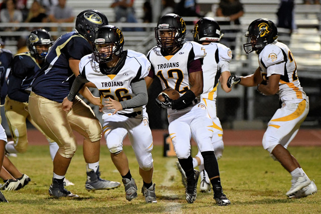 Peter Davis / Special to the Pahrump Valley Times Nickolas Redmond carries the football against the Desert Shields in Friday's loss. He had the longest carry for the Trojans of the night with a 78 ...