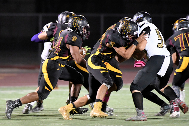 Peter Davis / Special to the Pahrump Valley Times Aaron Fuentes looks for running space during last week's game against Sunrise Mountain, which became the Trojans fourth victory of the year.