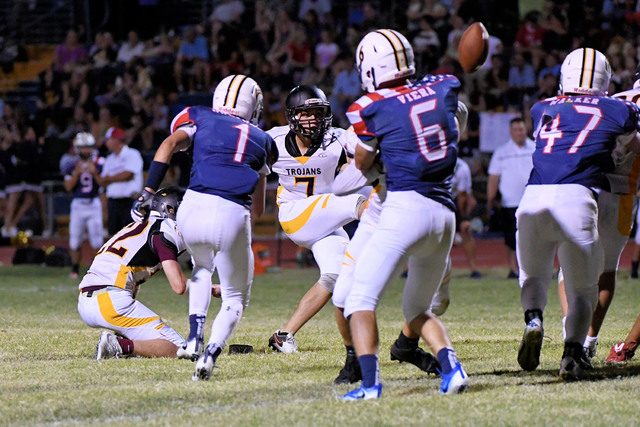 Peter Davis / Special to the Pahrump Valley Times  Boulder City is seen rushing Pahrump's kicker, Joey Sladek in September. The Trojans beat Boulder City 35-6 this year.