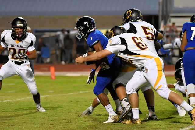 Peter Davis / Special to the Pahrump Valley Times Above, Trojans defenders trying to contain Jaguar running back Isaiah Morris, who ran for 117-yards rushing and couldn't be stopped.