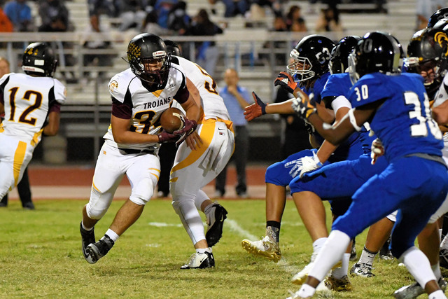 Peter Davis / Special to the Pahrump Valley Times   Nico Velazquez carries the ball for the Trojans towards a sea of blue. The play shows the deep penetration of the Jaguar defensive line, which w ...