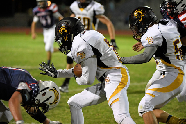 Peter Davis / Special to the Pahrump Valley Times Junior Dylan Coffman runs the ball against Boulder City last Friday. That game, the Trojans spread the rushing around and used 10 rushers for 207  ...