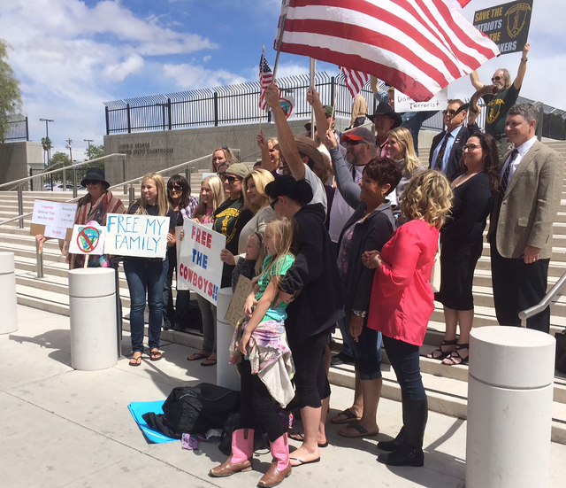 Protesters pose outside of the Lloyd George Federal Building in Las Vegas ahead of an arraignment hearing in April 2016. Seventeen defendants face charges stemming from the armed standoff in 2014  ...
