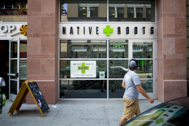 A pedestrian walks pass Native Roots Dispensary where different forms of recreational marijuana can be purchased in Denver, Colorado.  Elizabeth Page Brumley/Special to the Pahrump Valley Times