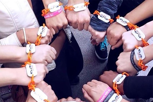 """Women wearing a bracelet made of orange plastic links meant to look like a chain were part of recent """"Break These Chains, Live Free"""" events to raise awareness about human trafficking in downto ..."""