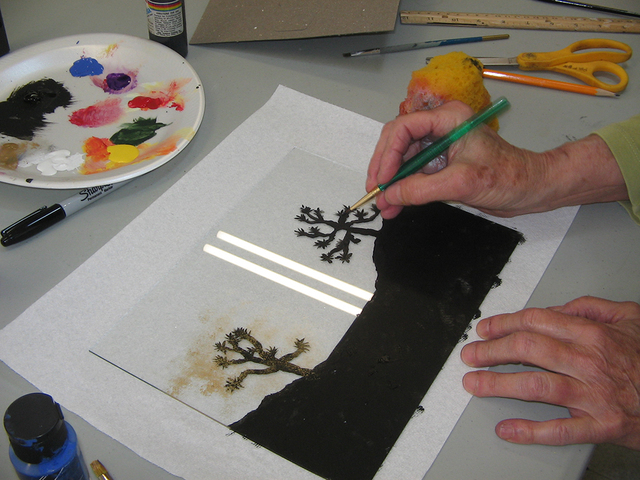Cheryl Tocco demonstrates the technique of reverse glass painting. She sketches and paints a scene on the back side of  glass from an old frame, and then flips it to  view the painting through  th ...