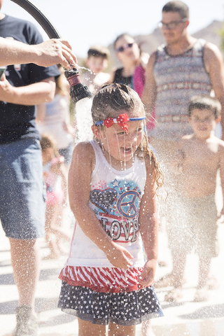 Alaina Hunt gets hosed down for the watermelon eating contest during the Fourth of July festivities in Beatty.