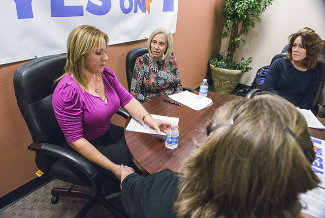 Lisa Lynn Chapman, right, with Nevada Network Against Domestic Violence, holds hands with domestic violnce victim during a news conference Wednesday at Safe House in Henderson. Advocates against d ...