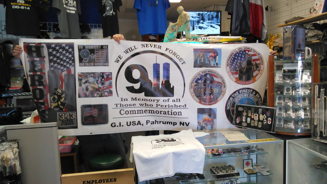 The owners of GI USA business display a custom-made banner in observance of Sunday's 9/11 ceremony in the Albertson's Plaza, 200 S Highway 160, on Sunday at 7 p.m. Past patriotic-themed events ...