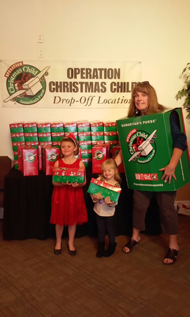 Michele Grabely, right, stands with two helpers, Aleah Dickerson, left, and Emma Richmond, center, at Trinity Assembly of God's drop off location for the annual Operation Christmas Child. The pr ...