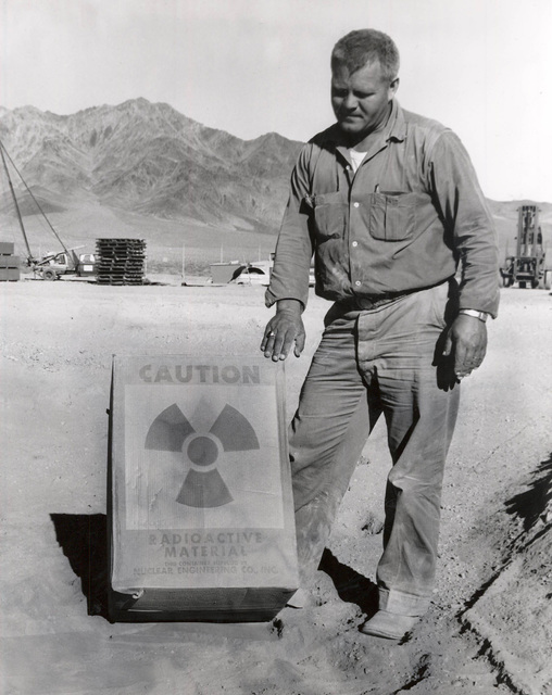 A worker stands by a radioactive materials sign in this undated photo at the former Nuclear Engineering Co. low-level nuclear waste landfill, 11 miles south of Beatty.  Las Vegas Review-Journal file