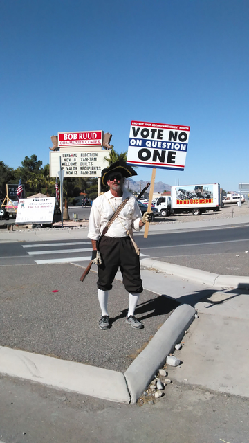 A man dressed as a Revolutionary War-era militia man near the polling place at Bob Ruud Community Center encourages voters to note no on State Ballot Question 1 which would expand background check ...