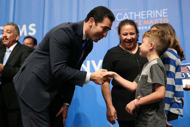 Congressman-elect Ruben Kihuen, left, shakes the hand of a young supporter during the Nevada State Democratic Party at the Aria in Las Vegas on General Election night Tuesday. The former state sen ...