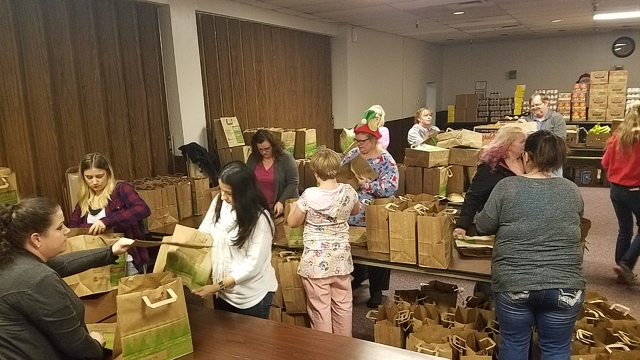 Volunteers, as shown in this Dec. 16 photo in the Tonopah Convention Center, bag produce as part of a Christmas meals distribution Dec. 17. David Jacobs/Times-Bonanza & Goldfield News