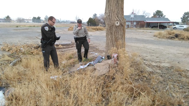 Nye County Sheriff's deputies look where several apparent Christmas gifts as well as purses containing credit cards were discovered underneath a tree at Discovery Park on Dec. 22. The sheriff' ...
