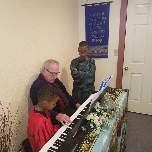 Musician James Dilworth Sr. of Reno practices piano prior to a Christmas program Dec. 24 inside The Little Church in Goldfield. Working with Dilworth are Elijah Broadnax, 10, right, and Ezekiel Br ...