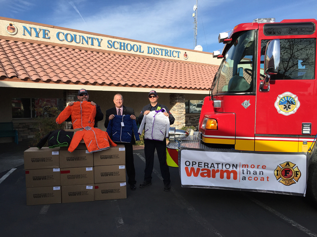 """Pahrump Valley Fire and Rescue Services firefighter/AEMT Jim Medici, left, holds one of 60 coats manufactured for """"Operation Warm, More Than A Coat,"""" destined for area school students. Medici  ..."""