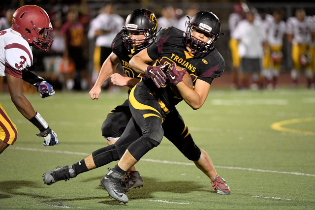 Peter Davis / Special to the Pahrump Valley Times   Nico Velasquez runs the ball against Del Sol. The Trojans hope to be able to run the ball on the ground this week at Boulder City.