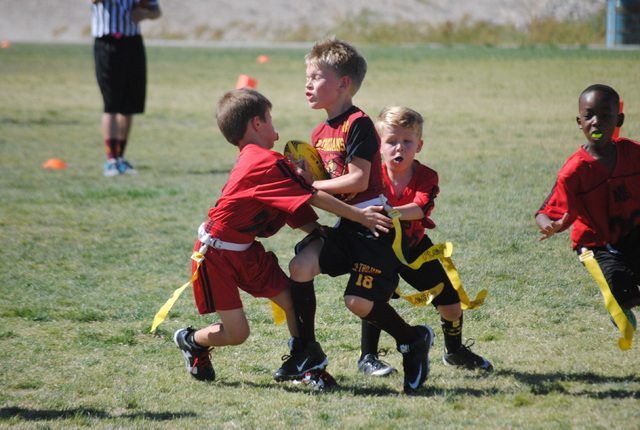 Kameron Stough keeps pushing forward to gain more yards with Pavicich players surrounding him during a Junior Trojans flag football game on Saturday.