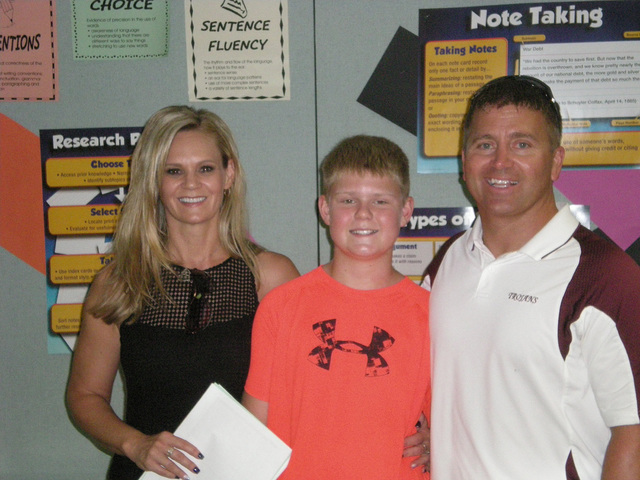 Trojans head wrestling coach Craig Rieger and his wife and son take the grand tour of the middle school.