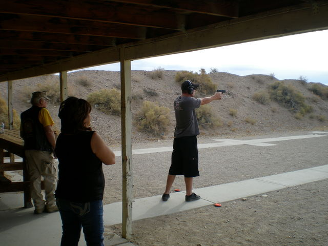 An unknown pistol shooter takes a shot at some clay pigeons lined up 30 yards away, tough shot.  Vern Hee / Pahrump Valley