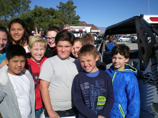 Vern Hee / Pahrump Valley Times Students at JG Johnson Elementary School gather around Tim Carolan's race car. Best in the Desert sent four race teams to the school and they set up in the parking lot.