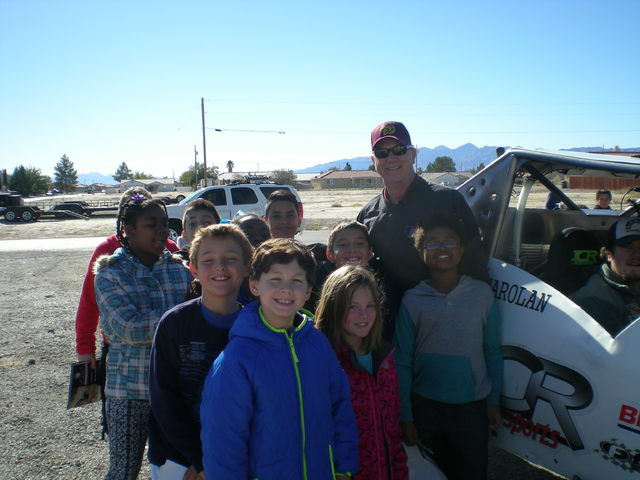 Vern Hee / Pahrump Valley Times Superintendent of schools, Dale Norton hangs with the kids in front of a Best in the Desert race car on Friday at JG Johnson.