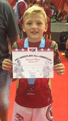 At left, Gunner Cortez (70 pounds)  holds up his certificat for finishing in seventh place in Greco-Roman wrestling at the Asics Kids Nationals in Wisconsin Dells. At right, Brennen Benedict (75 p ...