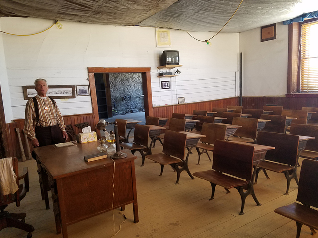 John Ekman, president of the Goldfield Historical Society, is shown inside Goldfield High School in this Aug. 6 photo.  The desks show in this photo were donated by the Fourth Ward School Museum i ...