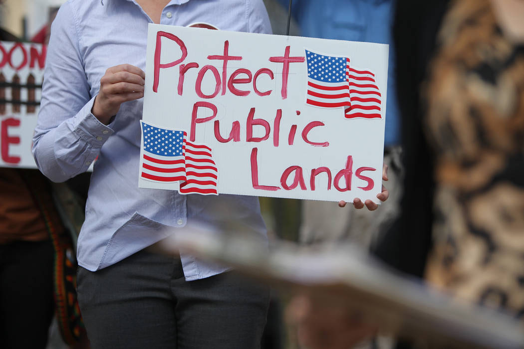 Jaina Moan holds a sign during a rally against Senate Joint Resolution 1, a proposition that will transfer federal public lands to the state of Nevada, outside of the Grant Sawyer Building in Las  ...